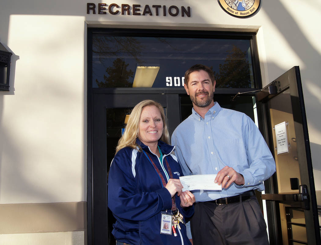 Boulder City Boulder City Sunrise Rotary President Tony Scheppmann presents a sponsorship check to Boulder City's Sports Coordinator Kelly Lehr for the youth floor hockey program. The Rotary club  ...