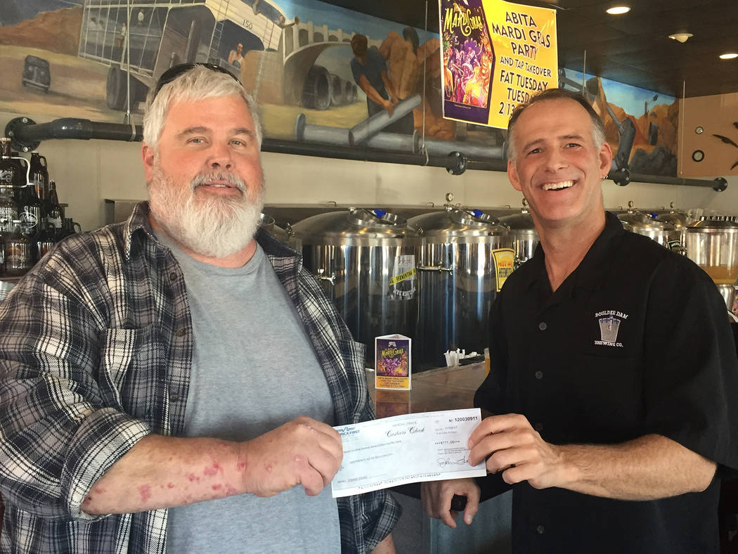 Boulder Dam Brewing Co. Michael Derby, left, president emeritus of Emergency Aid of Boulder City, accepts a check for $777, proceeds from the Oct. 21 Zombie Walk, from Todd Cook, owner of Boulder  ...