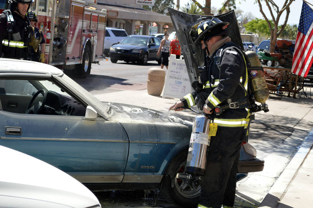Celia Shortt Goodyear/Boulder City Review Boulder City Firefighter Brian Shea puts out a fire that started in a 1981 Datsun 280 ZX on Friday in downtown Boulder City.