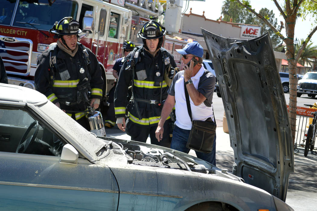 Celia Shortt Goodyear/Boulder City Review Boulder City Fire Department firefighters Brian Shea, left, and Daniel Schuster respond to a car fire in downtown Boulder City on Friday. Car owner Paul M ...