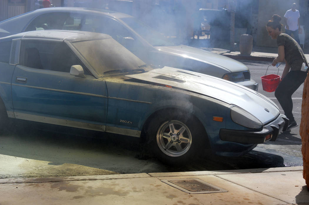 Celia Shortt Goodyear/Boulder City Review Crystal McLean, employee at the World Famous Coffee Cup Cafe, throws water on the fire in a 1981 Datsun 280 ZX that started smoking and erupted into flame ...