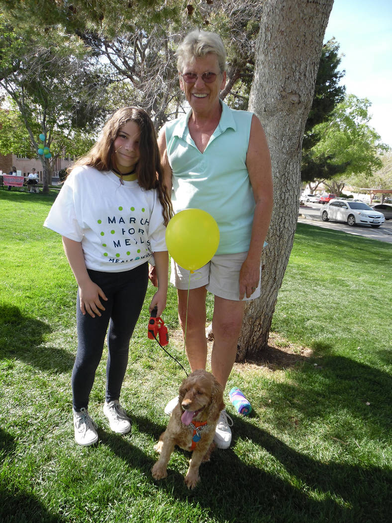 Hali Bernstein Saylor/Boulder City Review Airyanna Chavez, left, visits with Mona Goddard and her foster dog, Tweekers, during Saturday's Rock, Roll & Stroll fundraiser for the Senior Center o ...