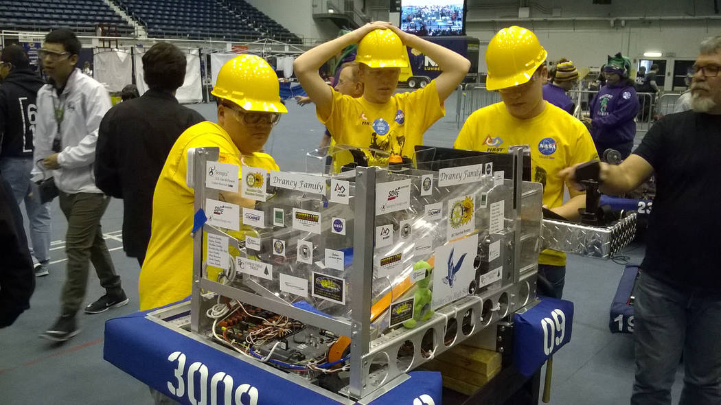 John Richner High Scalers members, from left, Cooper Cummings, Dustin Landerman and Wyatt Harling prepare the team's robot for another round of competition at a recent event.