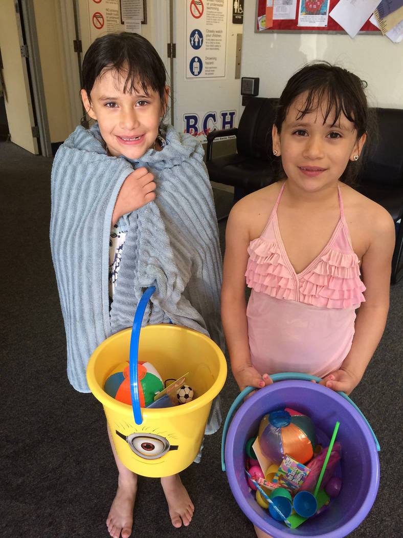 Hali Bernstein Saylor/Boulder City Review Twins Irene, left, and Nevaeh Lua collected a vareity of prizes during the second annual Easter pool plunge Saturday  at the Boulder City Municipal Pool.