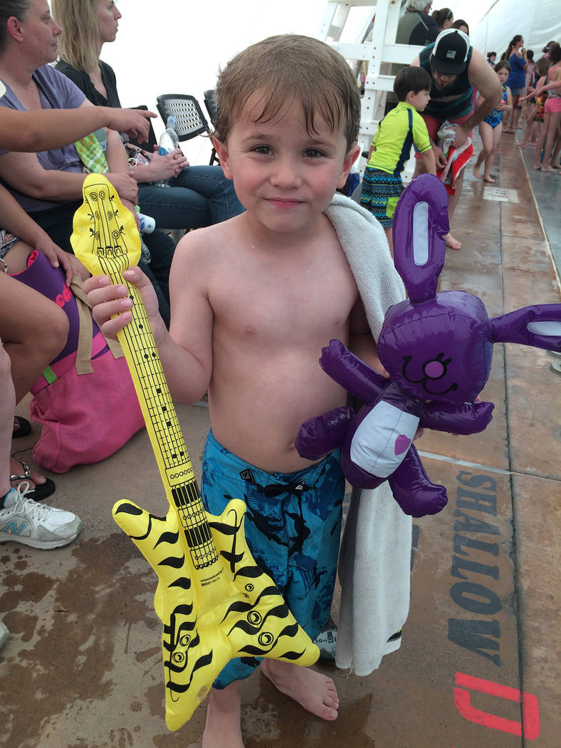 Hali Bernstein Saylor/Boulder City Review Five-year-old Cole Gansert of Boulder City shows off some of the treasures he found during the Easter pool plunge Saturday at the municipal pool.