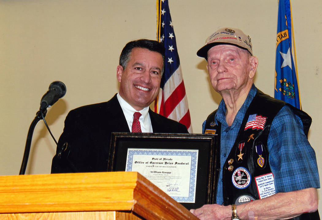 Nevada Department of Veterans Affairs Nevada Gov. Brian Sandoval, left, honors and recognizes Bill Knapp as April's veteran of the month. He visits the Southern Nevada Veterans Memorial Cemetery ...