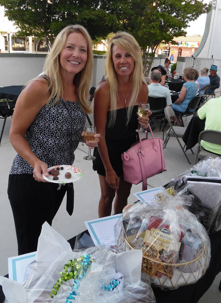 Hali Bernstein Saylor/Boulder City Review Natalie Cowdrey, left, and Julie Hill look over the silent auction baskets at Saturday's chocolate and wine tasting event presented by the Boulder City br ...