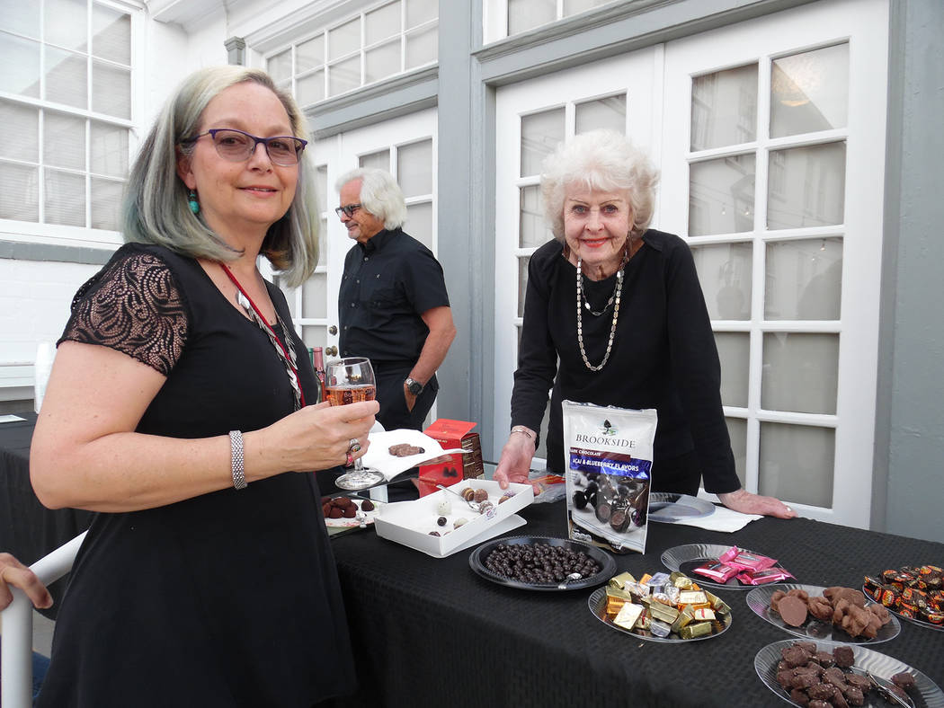 Hali Bernstein Saylor/Boulder City Review Donna Hieleman, left, looks over the selection of chocolates available as Barb Morris makes recommendations during Saturday's chocolate and wine tasting e ...