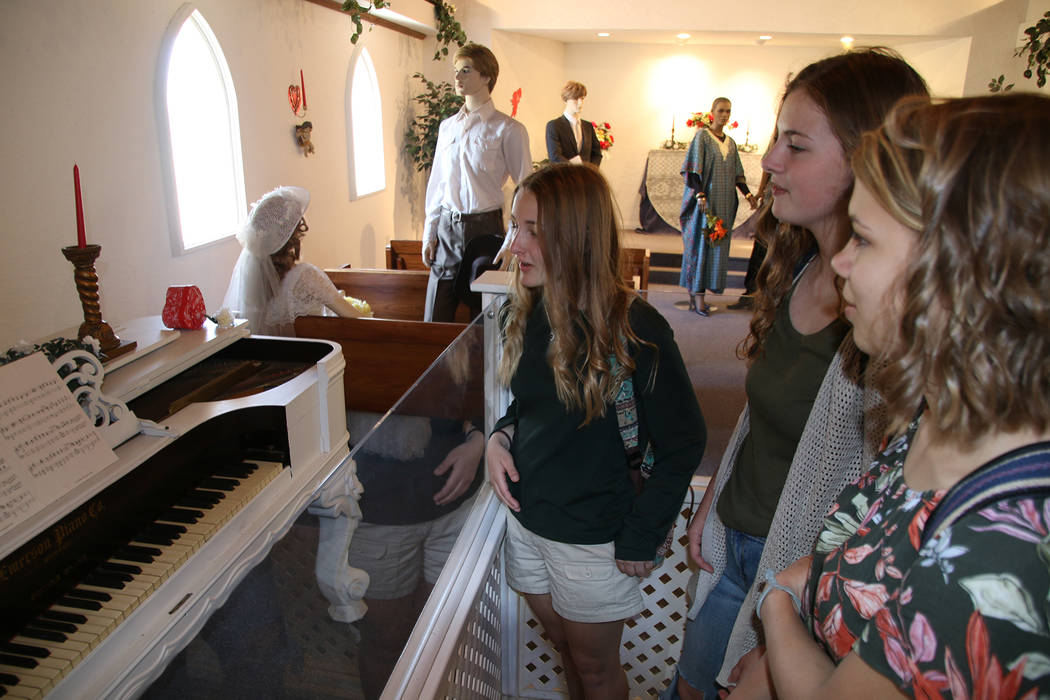 Boulder City High School yearbook Kylee Shamo, from left, Kristina Davidson, and Lauren Stewart admire a vintage piano that had once been played during weddings at the Candlelight Wedding Chapel d ...
