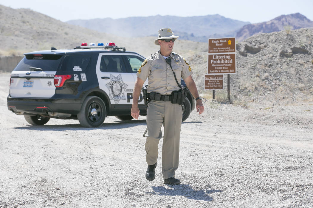 Bridget Bennett Las Vegas Review-Journal @bridgetkbennett Metropolitan Police Department Sgt. Eugene Gallagher stand guard at an entrance to Eagle Wash Road, which leads to the crime scene, at Lak ...