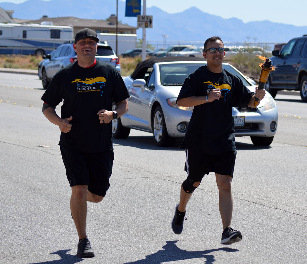 Celia Shortt Goodyear/Boulder City Review Boulder City Police Department Detective Todd Huff, left, and officer Armando Salazar carry the Special Olympic Nevada torch along Nevada Highway to Veter ...