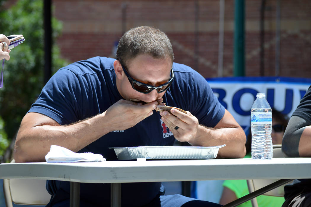 Celia Shortt Goodyear/Boulder City Review Boulder City firefighter Nigel Walton eats his ribs as fast as he can during the rib-eating contest at the Best Dam Barbecue Challenge on Saturday.