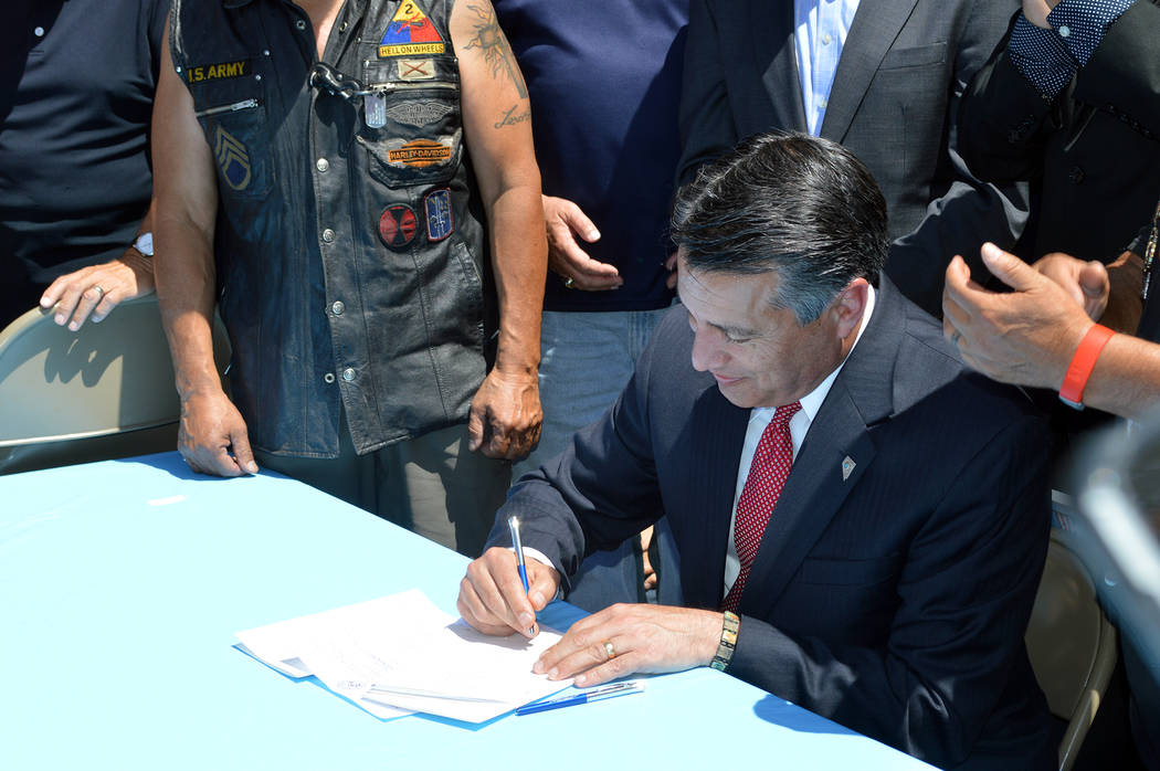 Celia Shortt Goodyear/Boulder City Review Gov. Brian Sandoval signs Senate Bill 191, which standardizes eligibility for benefits for service-related disabilities for veterans, into law Monday, fol ...