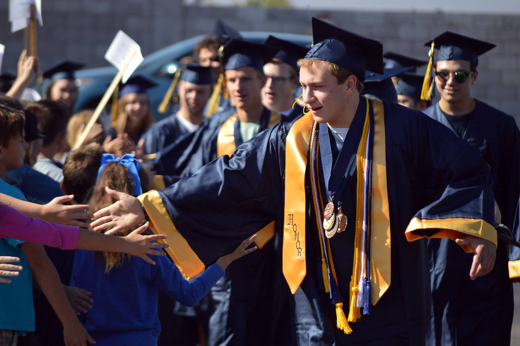 Celia Shortt Goodyear/Boulder City Review Boulder City High School co-valedictorian Michael Martinelli high fives students of the elementary schools during the 2017 Grad Walk on Monday morning.