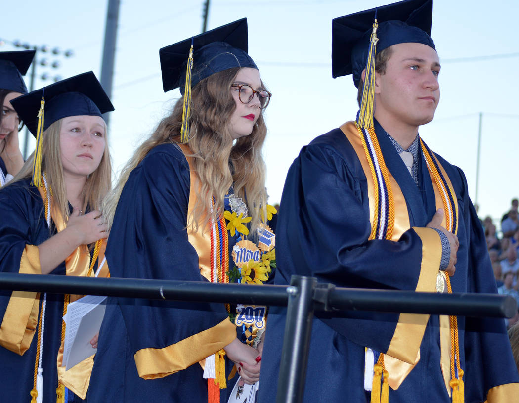 Celia Shortt Goodyear/Boulder City Review Salutatorian Alea Lehr, left, and valedictorians Mira Newby center, and Michael Martinelli listen to the national anthem during Boulder City High School's ...