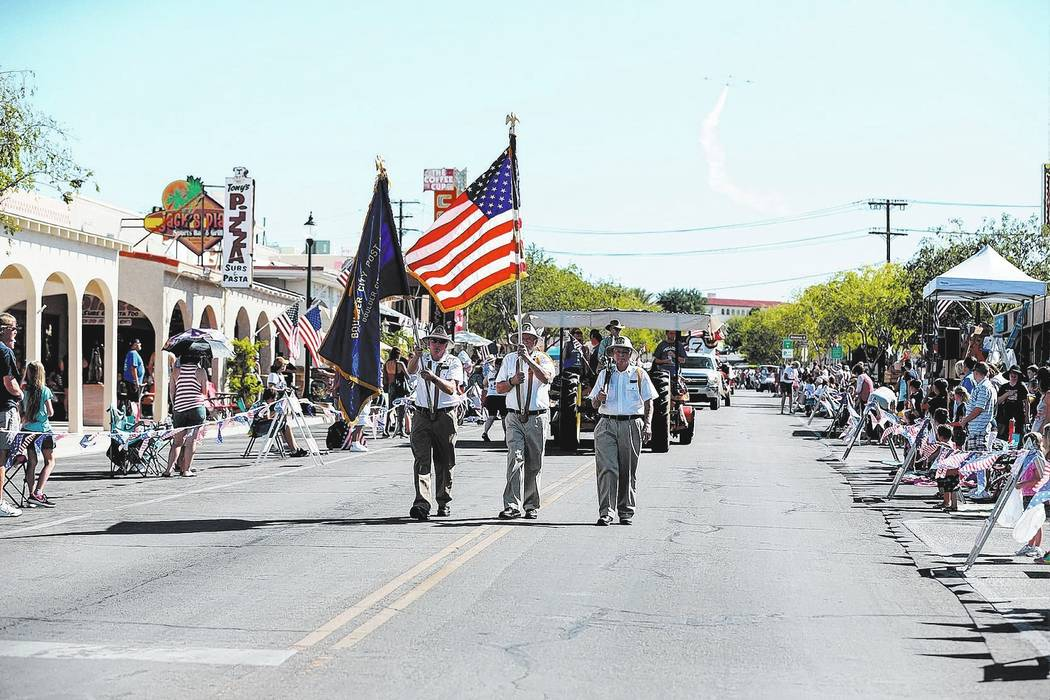 Members of the American Legion, Boulder City Post 31, carry the colors at the start of the 68th annual Damboree parade, as the Boulder City Veterans Flying Group makes its way over head in Boulder ...
