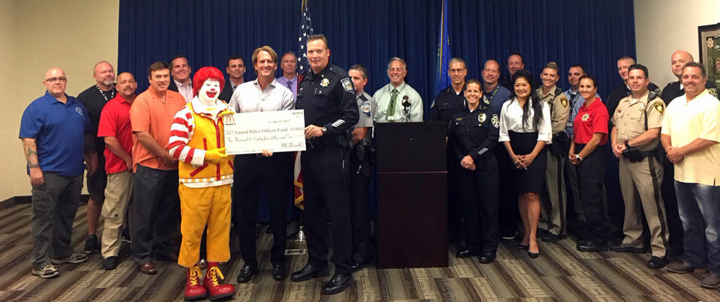 Metropolitan Police Department Ronald McDonald presents a check for more than $10,000 to the Injured Police Officers Fund that supports local law enforcement agencies, including Boulder City Polic ...