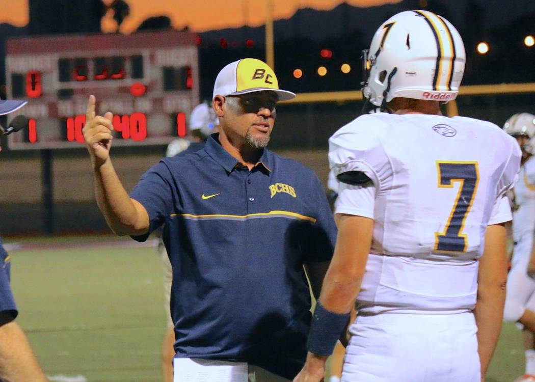 Laura Hubel Boulder City head coach Chris Morelli instructs quarterback Taylor Hatchel during a time out against Valley High School on September 16.
