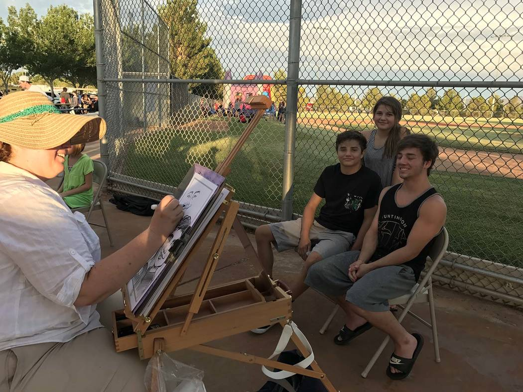 Hali Bernstein Saylor/Boulder City Review Celestia Ward, left, draws a caricature of siblings, from left, Skyler, Lexie and Tanner Hunt, who were visiting from Colorado and attended National Night ...