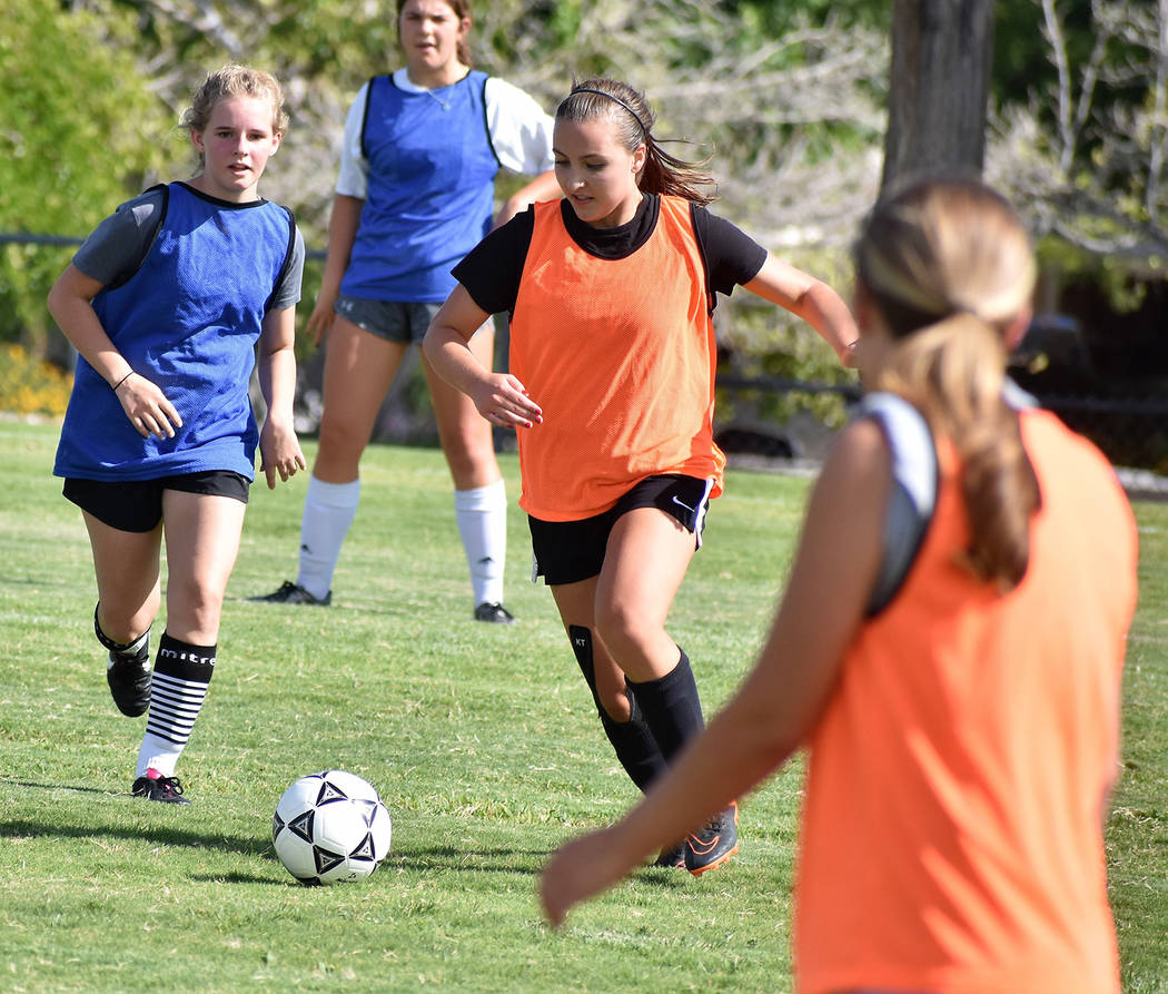 Robert Vendettoli/Boulder City Review Boulder City High School senior midfielder Sydney Manns, right, charges downfield pass defenders during the Aug. 15 practice. Manns, who sat out last season w ...