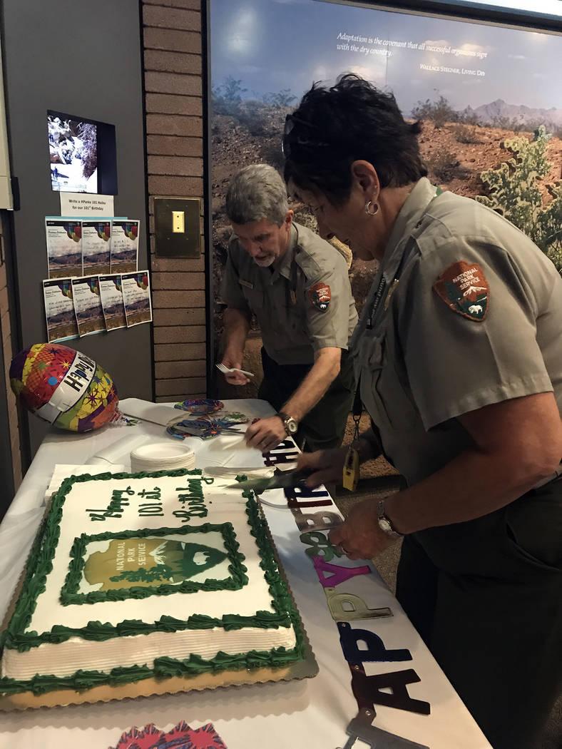Hali Bernstein Saylor/Boulder City Review Patrick Gubbins, deputy superintendent of Lake Mead National Recreation Area, and Lynn Neufeld, Alan Bible Visitor Center lead ranger, serve cake on Frida ...