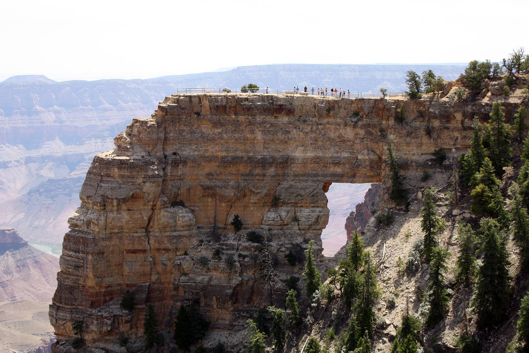 Deborah Wall Hikers stand above Angels Window just a five minute hike from Cape Royal Road at the North Rim of the Grand Canyon in Arizona.