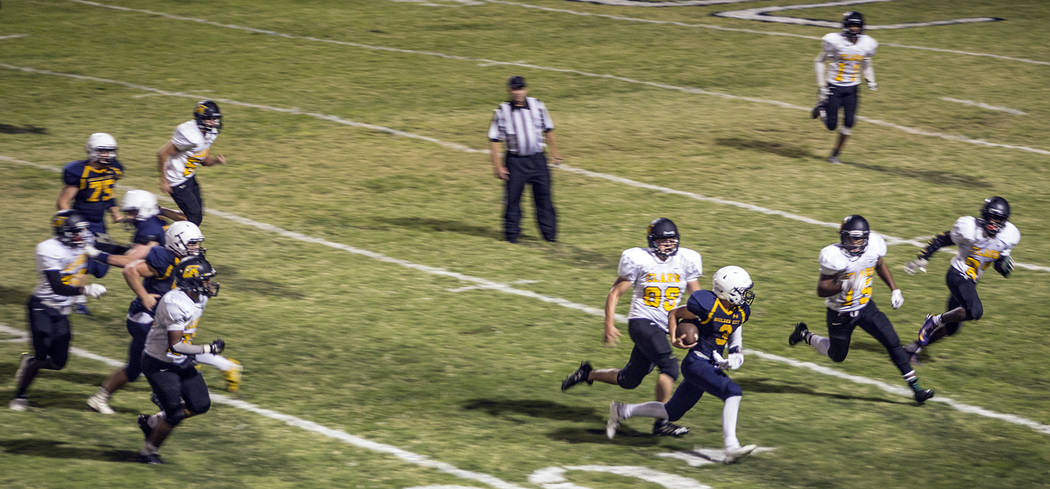 Oksana Saulenko/Boulder City Review During his first career start for Boulder City High School on Friday junior Shaun Jones, center, rushed for 73 yards and a touchdown on 17 carries, as well as c ...