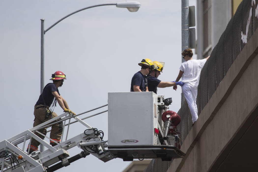 Erik Verduzco/Las Vegas Review-Journal A woman hanging off the Mandalay Bay overpass and above the northbound lanes of Interstate 15 is rescued by the Clark County Fire Department in Las Vegas on  ...