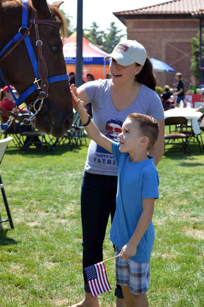 Celia Shortt Goodyear/Boulder City Review Santana Harper and her son, Briggs, get to know Odie, the first member of Boulder City's Mounted Police Unit during the Hero and First Responder Appreciat ...