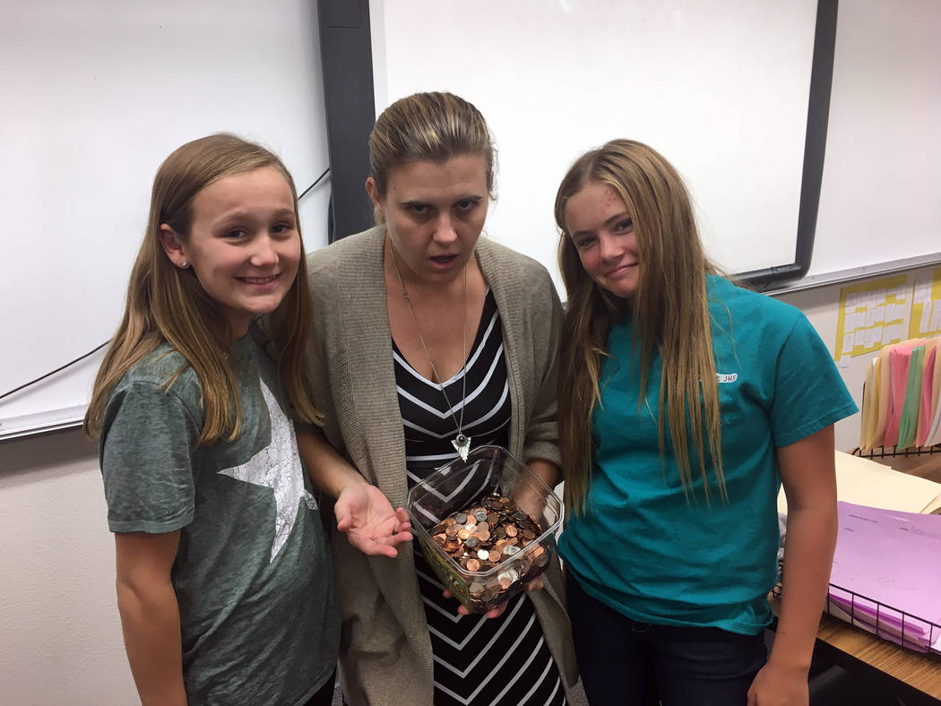 Garrett Junior High School  Algebra teacher April Acosta, center, expresses her sadness about the number of pennies in her Quarter Wars classroom jar along with student council members Ella Morris ...