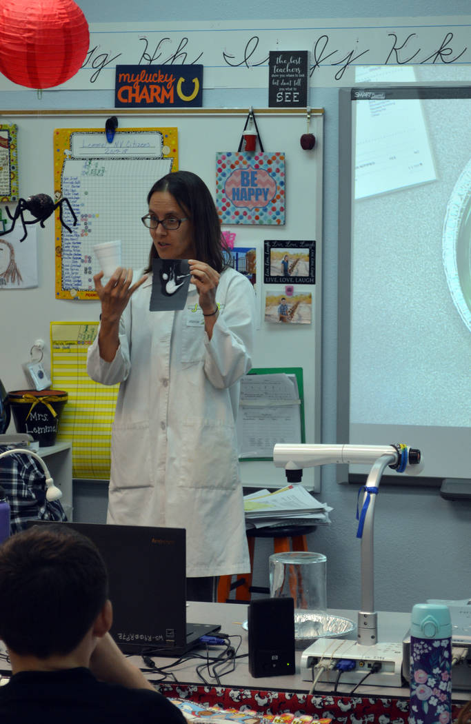 Celia Shortt Goodyear/Boulder City Review Science Mom Jenny Ballif shows students in Angie Lemmel's fourth-grade class at King Elementary School on Tuesday how plastic can be dissolved.