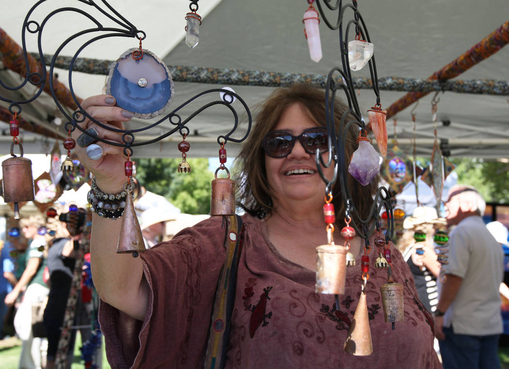 Gabriella Benavidez/Las Vegas Review-Journal Kay Koning looks at handmade wind chimes during Art in the Park on Saturday in downtown Boulder City.