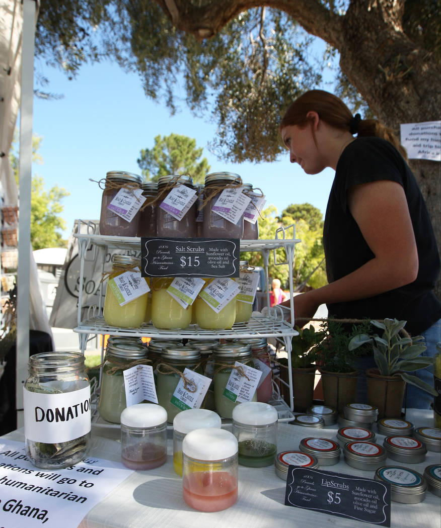 Gabriella Benavidez/Las Vegas Review-Journal Lizzy Taggard, 16, with Boulder City Soap & Candle Co., bags a purchase for a customer during the Art in the Park festival in Boulder City on Saturday.