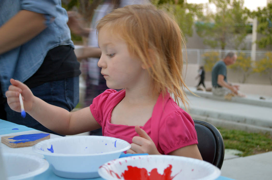 Celia Shortt Goodyear/Boulder City Review Four-year-old Amelia Solberg paints a wooden Nevada plaque at Friday's benefit concert at the library. Ruben's Wood Craft and Toys donated the plaques.