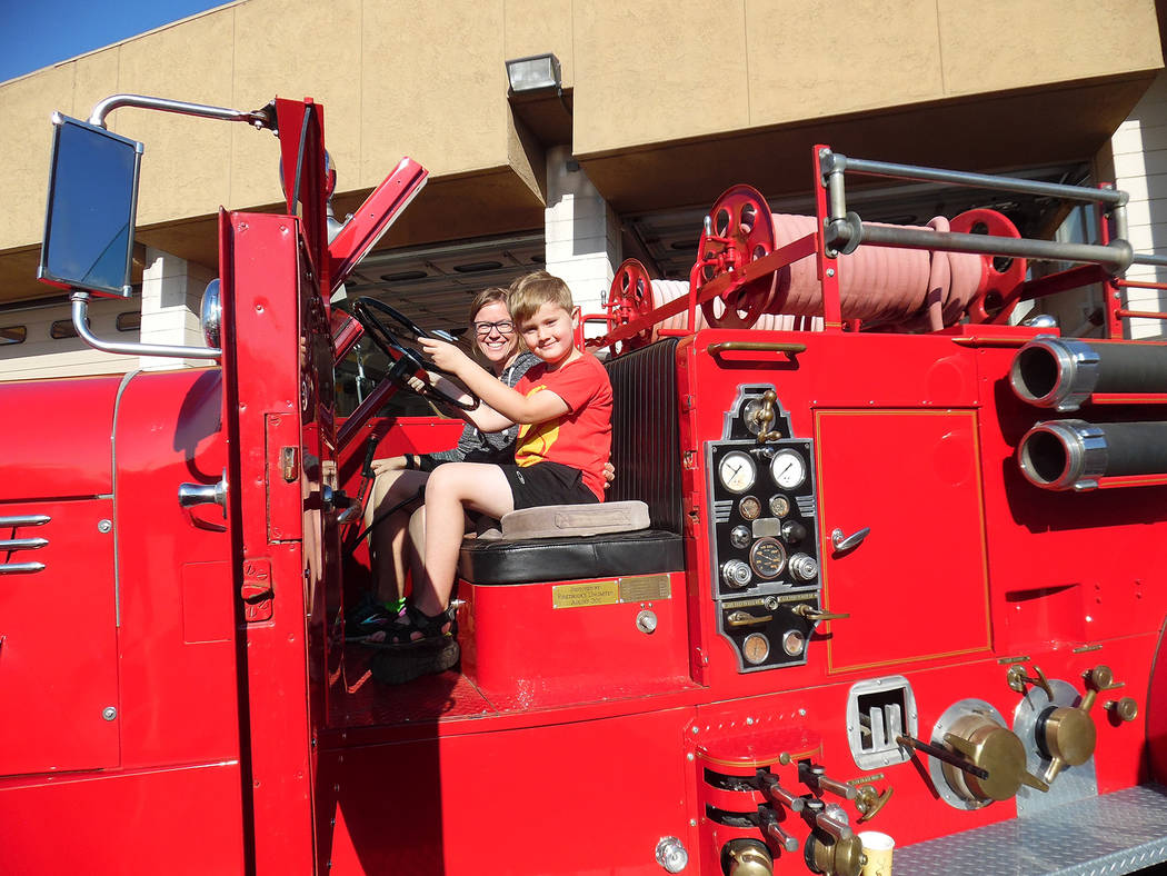 Hali Bernstein Saylor/Boulder City Review Errol Tietjen, 6, and his mother, Erica Tietjen of Boulder City climbed aboard an old fire truck from the Nevada National Security Site during Boulder Cit ...