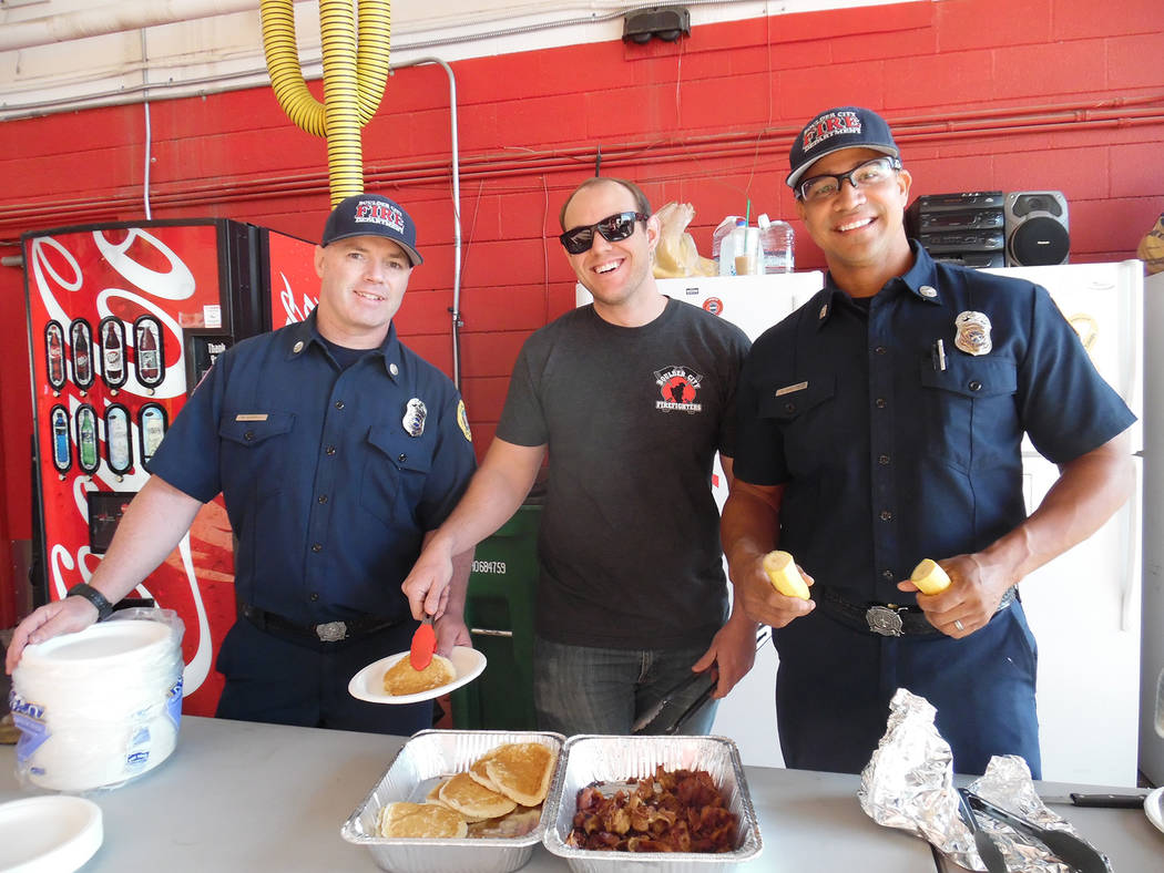 Hali Bernstein Saylor/Boulder City Review Boulder City Firefighters, from left, Mike Gabiola, Nick Giles and Harold Hadley were among those dishing up pancakes, bacon and bananas Saturday as the d ...