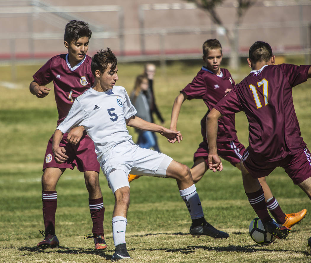Oksana Saulenko/Boulder City Review Boulder City High School freshman Julian Balmer strives to keep the ball away from three players from Pahrump Valley in the Eagles' 2-2 tie game on Saturday.