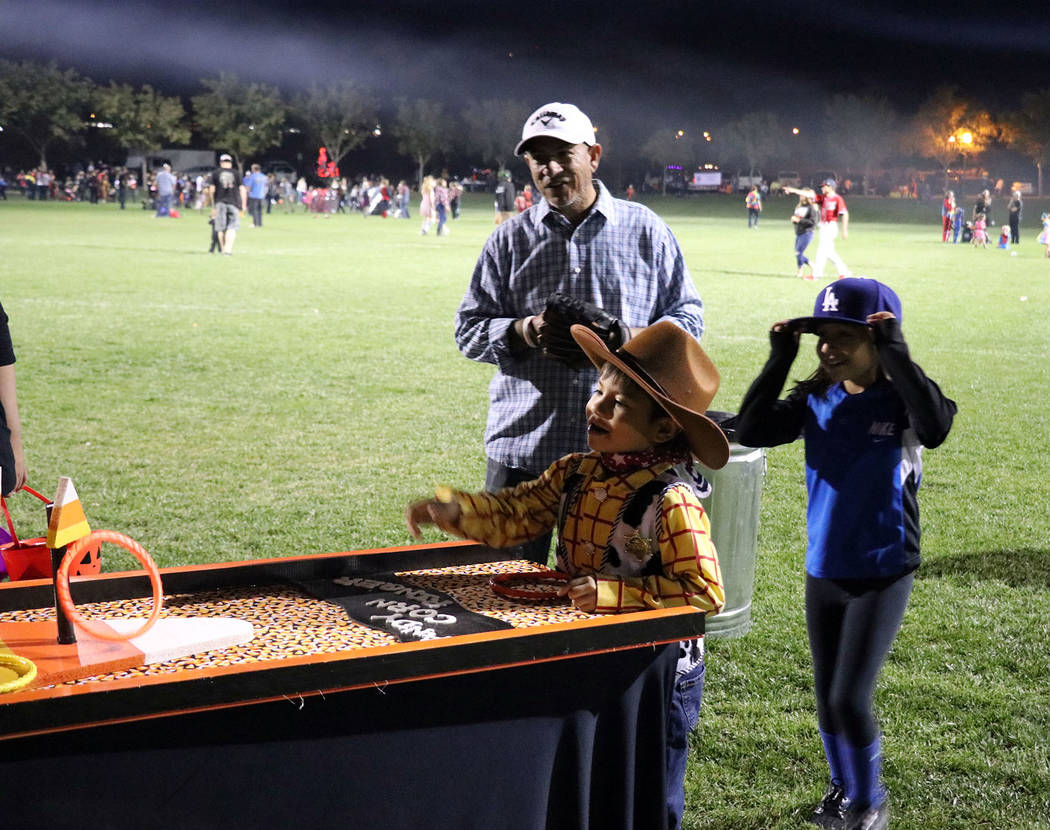 """Tristin Phelps/Boulder City Review A young boy, dressed as Woody from """"Toy Story,"""" tosses rings around the candy corn loops to win a prize during the annual Trunk or Treat celebration Saturday at  ..."""
