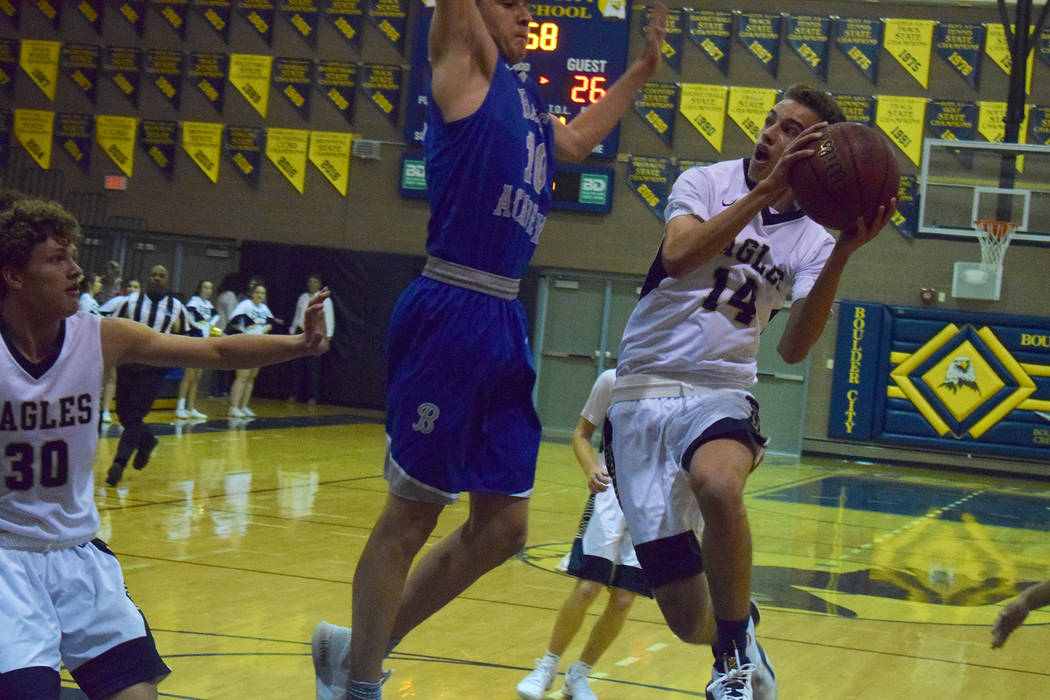 Robert Vendettoli/Boulder City Review Boulder City High School junior guard Karson Bailey, right, soars through the air midway through the first quarter, attempting a layup, during Tuesday's seaso ...