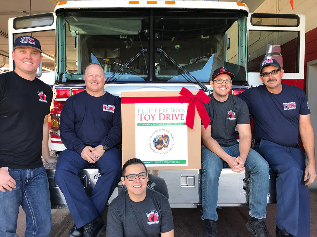 Boulder City Boulder City Firefighters, from left, Carl Ford, Denzil Mooney, Alexander Zoukas, Nicholas Giles and Jon Kingma, are helping with this year's Fill the Truck toy drive sponsored by the ...
