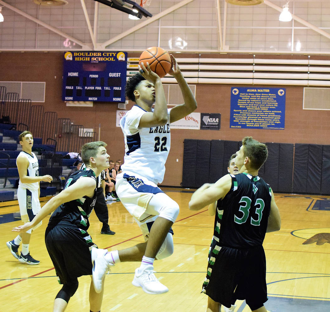 Robert Vendettoli/Boulder City Review Boulder City High School junior forward Derrick Thomas soars through the air over a pair of Virgin Valley defenders during their Dec. 14 game. Thomas scored a ...