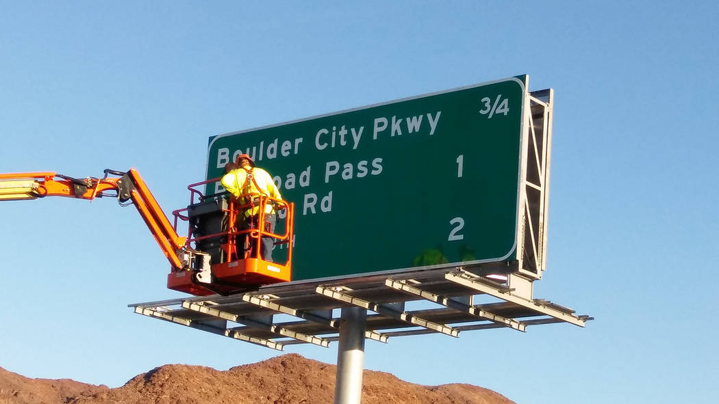 Val Olsen/Boulder City Review Nevada Department of Transportation workers install the corrected Boulder City Parkway sign on the southbound portion of Interstate 11 on Friday. NDOT's portion of th ...