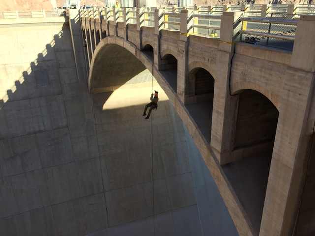 Photo courtesy Bureau of Reclamation Nathaniel Gee hangs from a rope while inspecting the bridge over the Arizona spillway at Hoover Dam on Oct. 19, 2016.