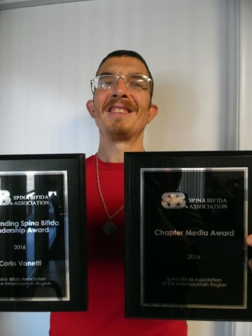 Carlo Vanetti shows off two of the awards he was given for his efforts to promote awareness of spina bifida during the national associations convention earlier this year in Minneapolis, Minnesota. ...