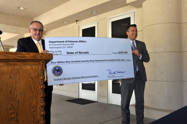 U.S. Department of Veterans Affairs Veterans Cemetery Grants Program Director George D. Eisenbach Jr., left, presents Nevada Gov. Brian Sandoval with a check for $4.9 million during a ceremony Fri ...