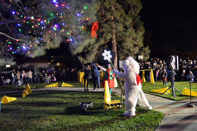 Max Lancaster/Boulder City Review  Boulder City residents cheered on the holiday season as Jingle Cat used a magic wand to light the community Christmas tree during the Christmas tree lighting at  ...