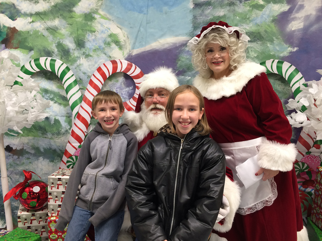 Hali Bernstein Saylor/Boulder City Review Ivan, 7, and Valerie Peterson, 10, visit with Santa and Mrs. Claus during Santa's Picture Party presented by the Boulder City Chamber of Commerce on Satur ...