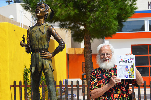 "Rudy Kraft poses in front of Mary Zimmerman's Peter Pan statue on Nevada Way. Kraft is the author/illustrator of the coloring book ""Let's Color Hoover Dam."" Max Lancaster/Boulder City Review"