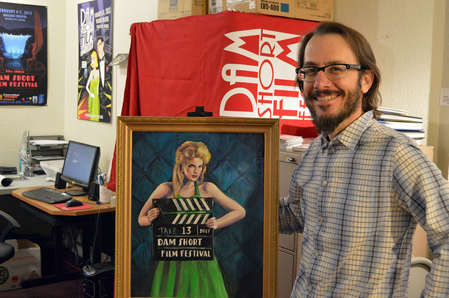 Max Lancaster/Boulder City Review Lee Lanier, executive director and co-founder of the Dam Short Film Festival, poses in front of this year's poster art for the 13th annual event, which will be he ...