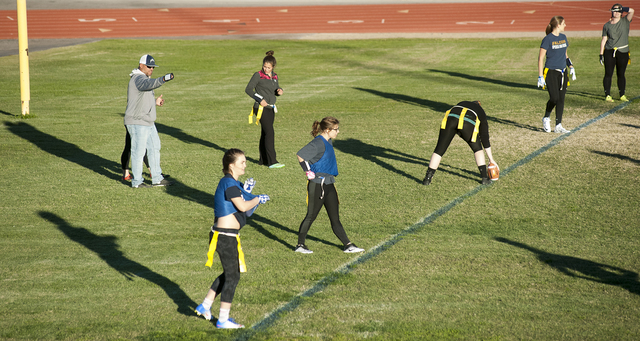 Steve Andrascik/Boulder City Review Boulder City High School's flag football head coach Chris Morelli, far right, and his team cast long shadows during practice Friday.